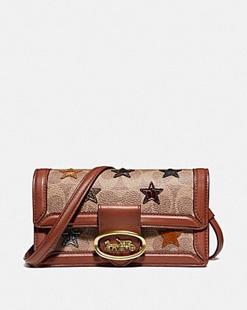 riley convertible belt bag in signature canvas with star applique and snakeskin detail